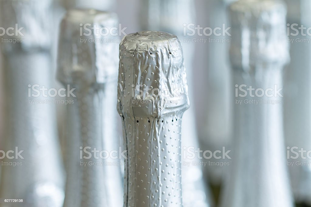 Silver champagne bottle necks and top caps at standing the stock photo