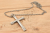 Silver christian cross with small diamonds on wooden board