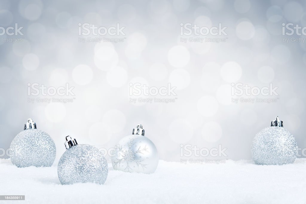 Silver Christmas baubles on snow with a silver background stock photo