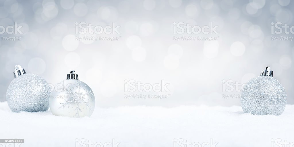 Silver Christmas baubles on snow with a silver background royalty-free stock photo
