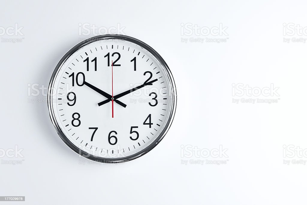 A silver classic wall clock on a white wall stock photo