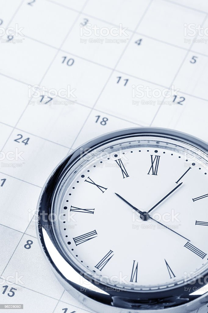 Silver clock on a paper calendar royalty-free stock photo
