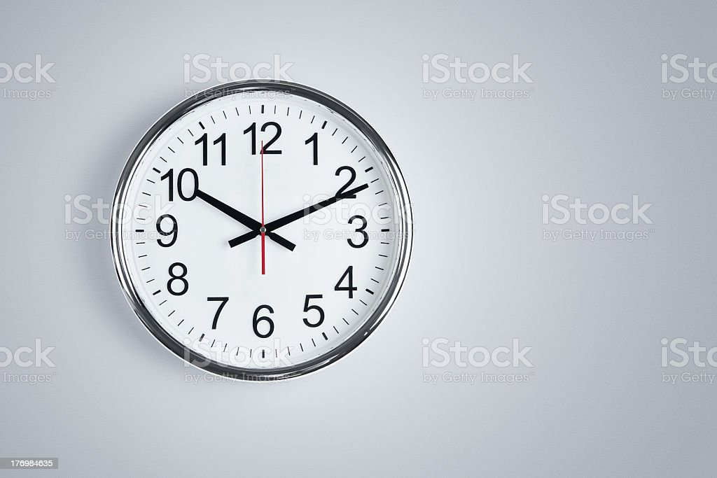 Silver clock with a red second hand set to 1010 stock photo