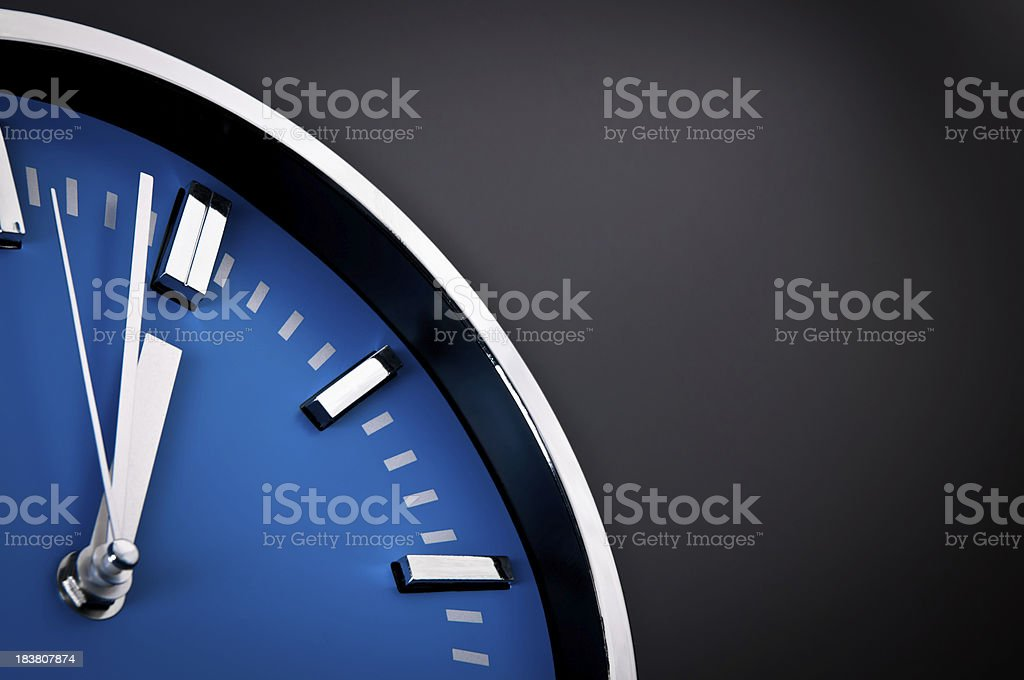 Silver clock with blue clock face showing 11:59 stock photo