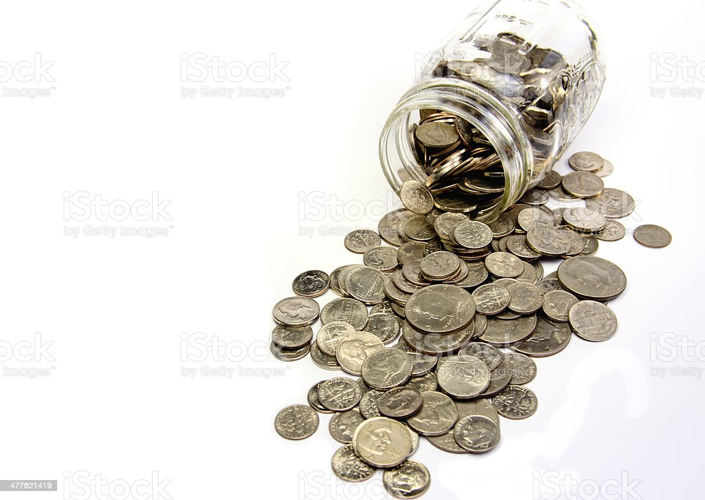 Silver Coins Spilling From Glass Jar stock photo