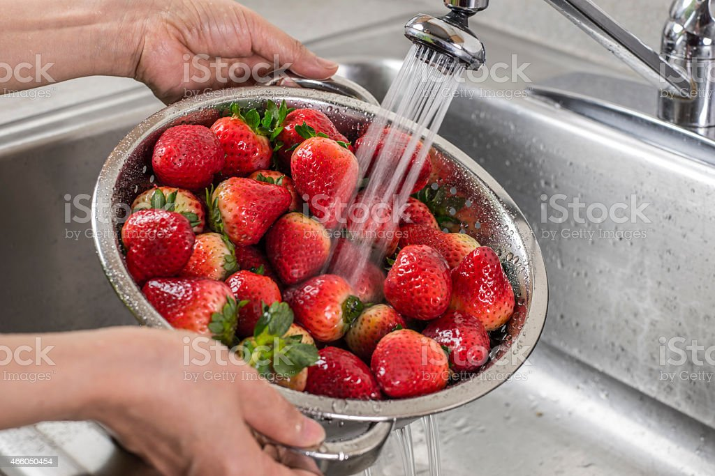 A silver colander full of strawberries being rinsed stock photo