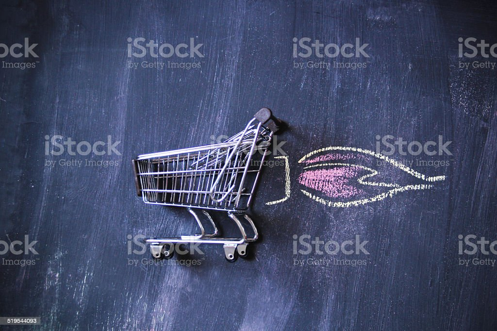 Silver color miniature shopping cart on black background stock photo