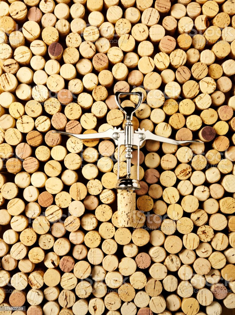Silver Cork Screw and a Background of Corks royalty-free stock photo