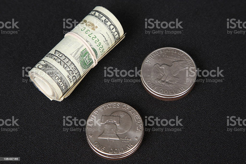 Silver dollars and a roll of twenties royalty-free stock photo