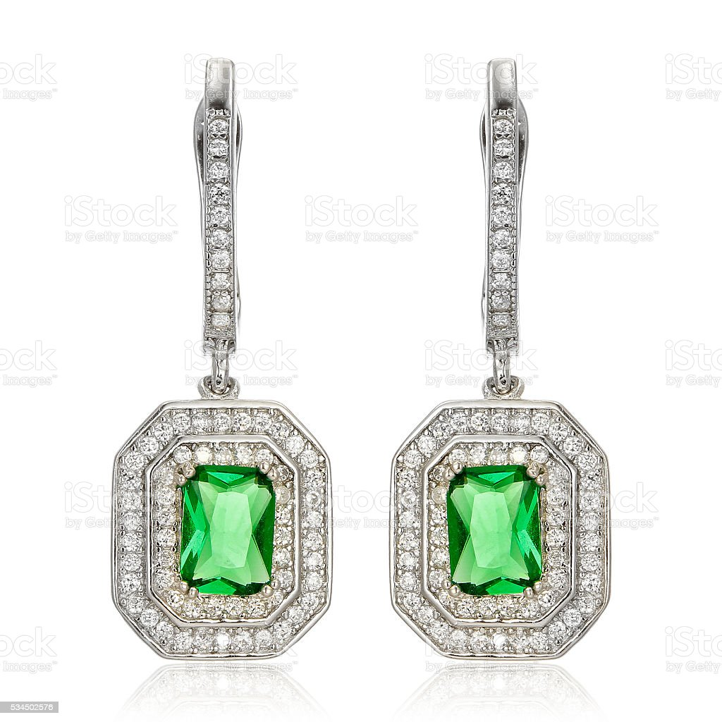 Silver earrings with emeralds isolated on white stock photo