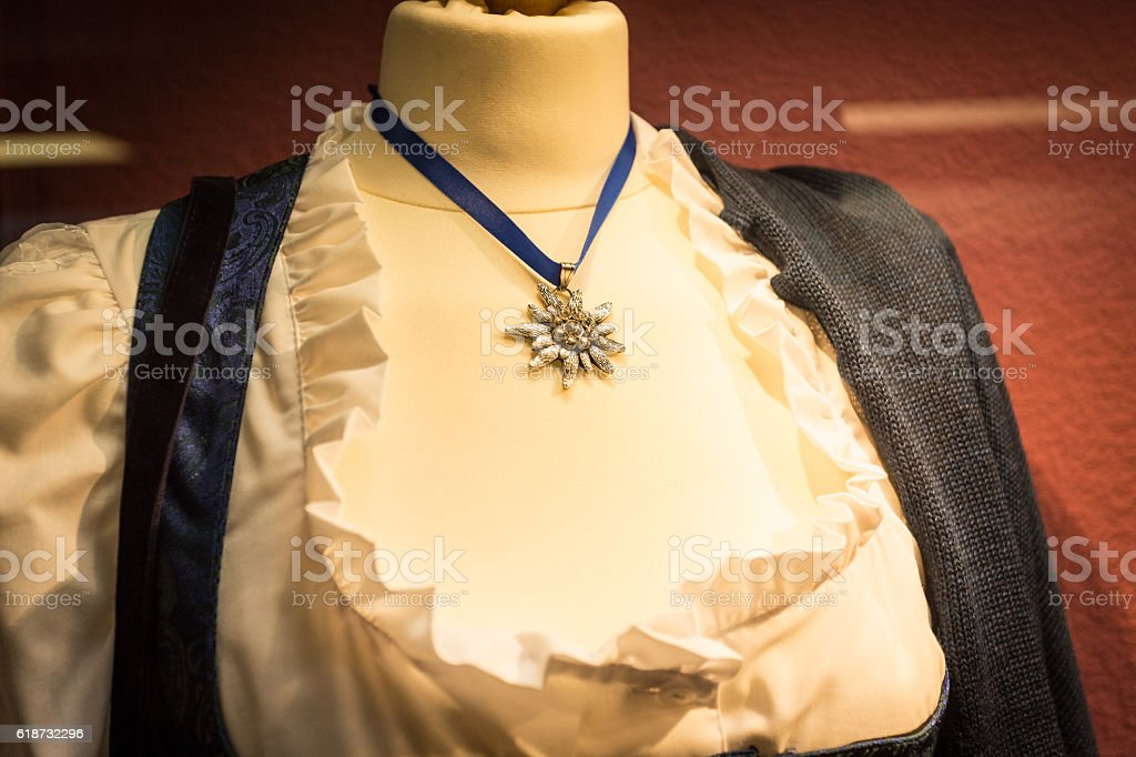 Silver edelweiss pendant on traditional austrian female costume stock photo