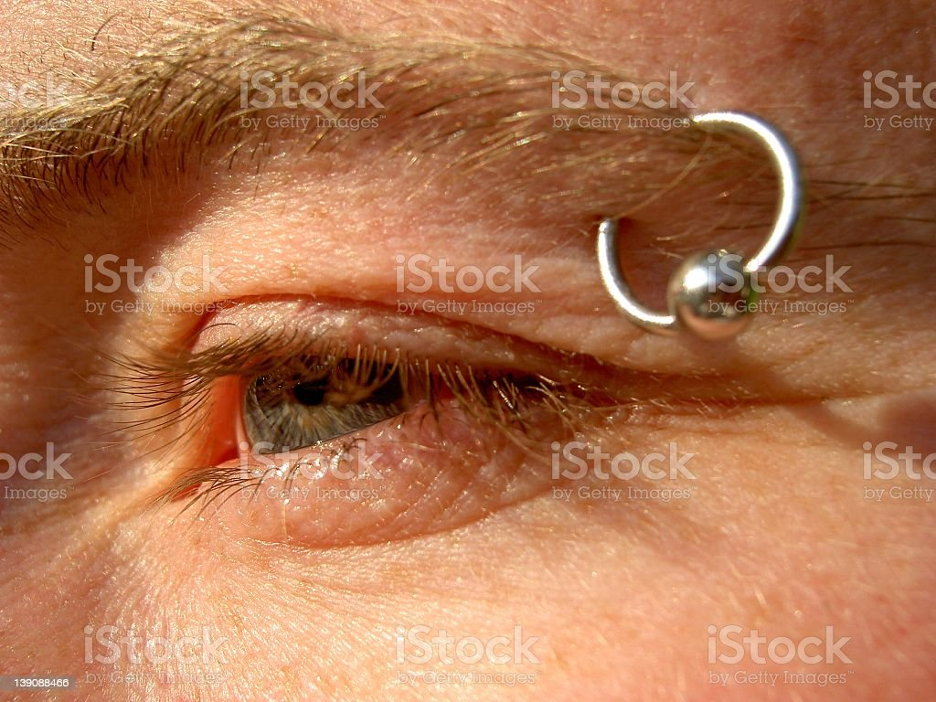 Silver eyebrow piercing with large ball stock photo