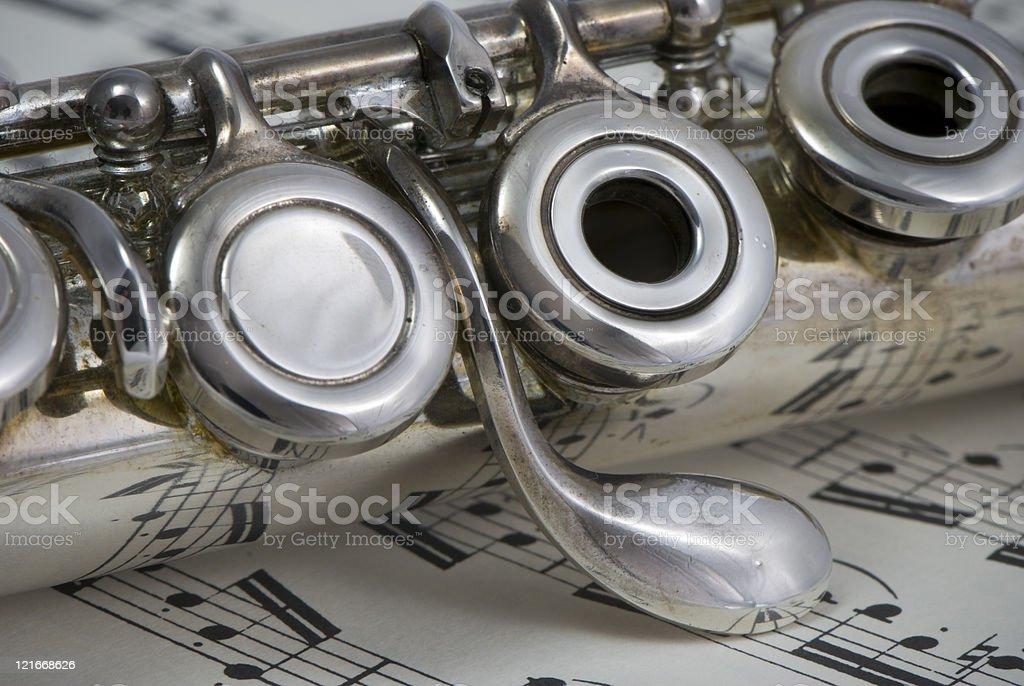Silver flute, macro, on sheet music royalty-free stock photo