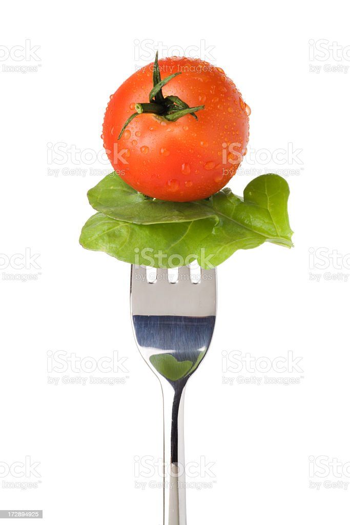 Silver fork holding a salad leaf and fresh-cut tomato stock photo