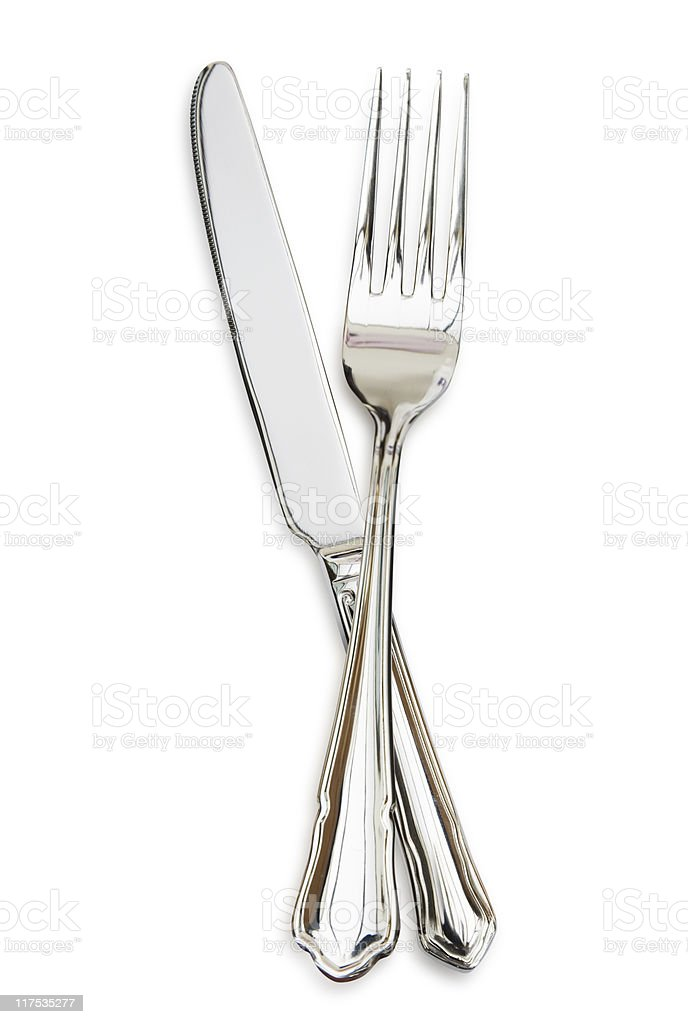 Silver fork sitting across a silver knife stock photo