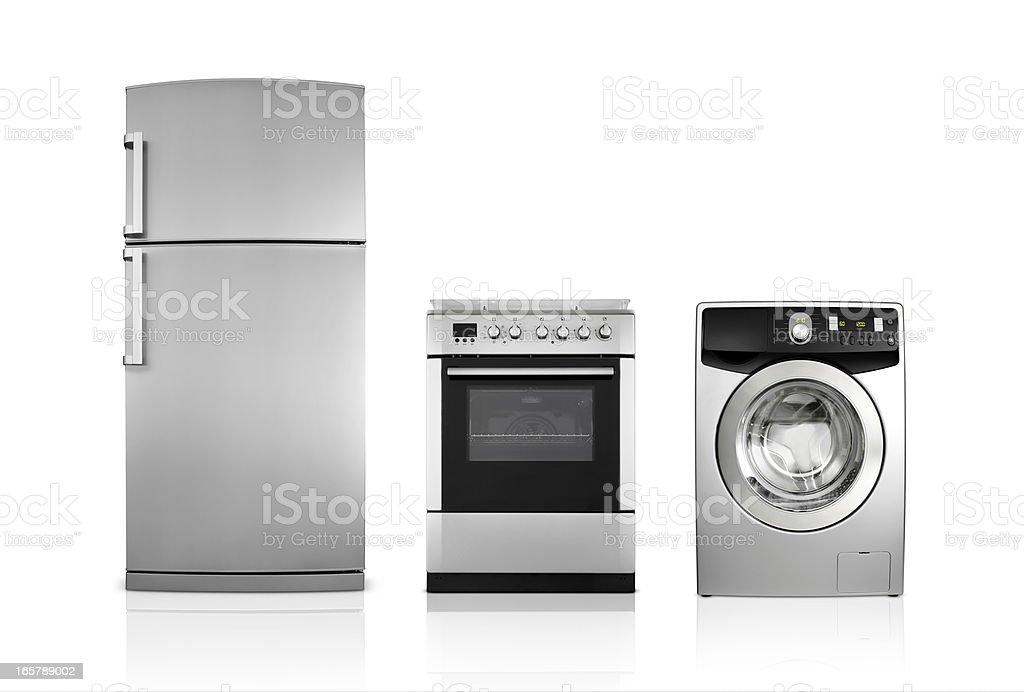 A silver fridge, an oven and dryer lined up side by side stock photo