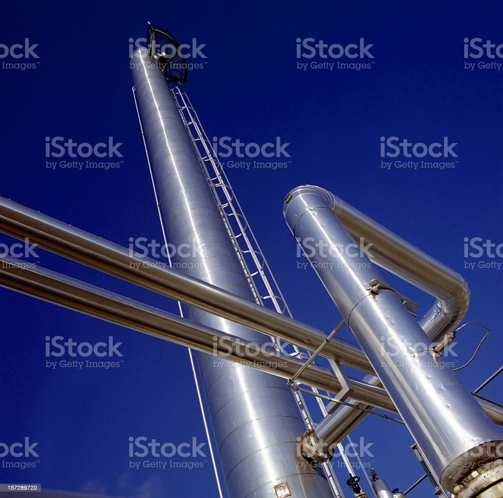 Silver Gas Plant Towers Against Blue Sky royalty-free stock photo