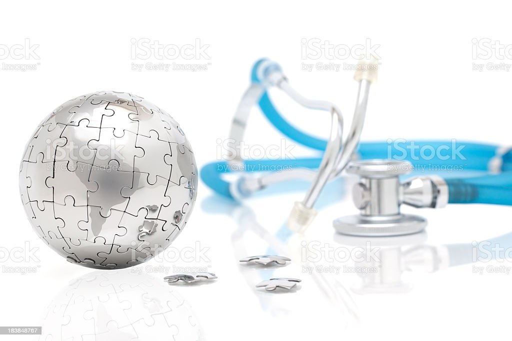 Silver globe made of puzzle pieces with blue stethoscope stock photo
