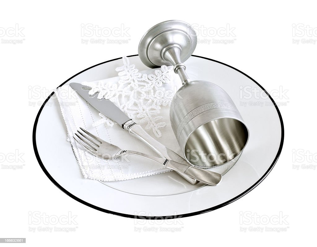 Silver goblet, fork and knife on a white plate royalty-free stock photo