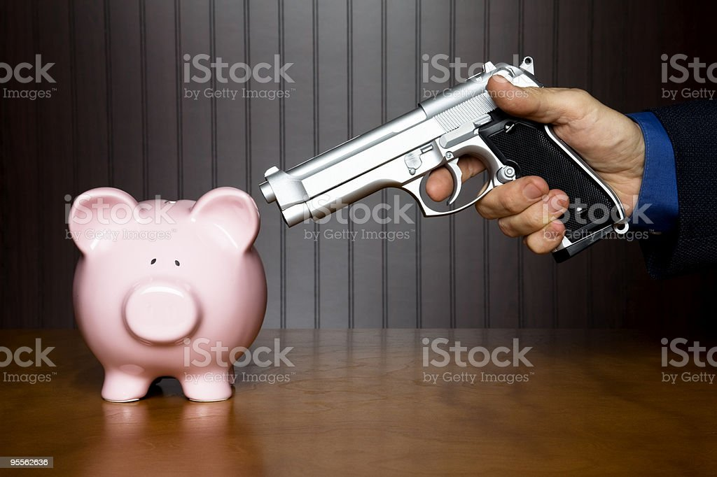 Silver gun pointed at pink piggy bank to give up its money stock photo