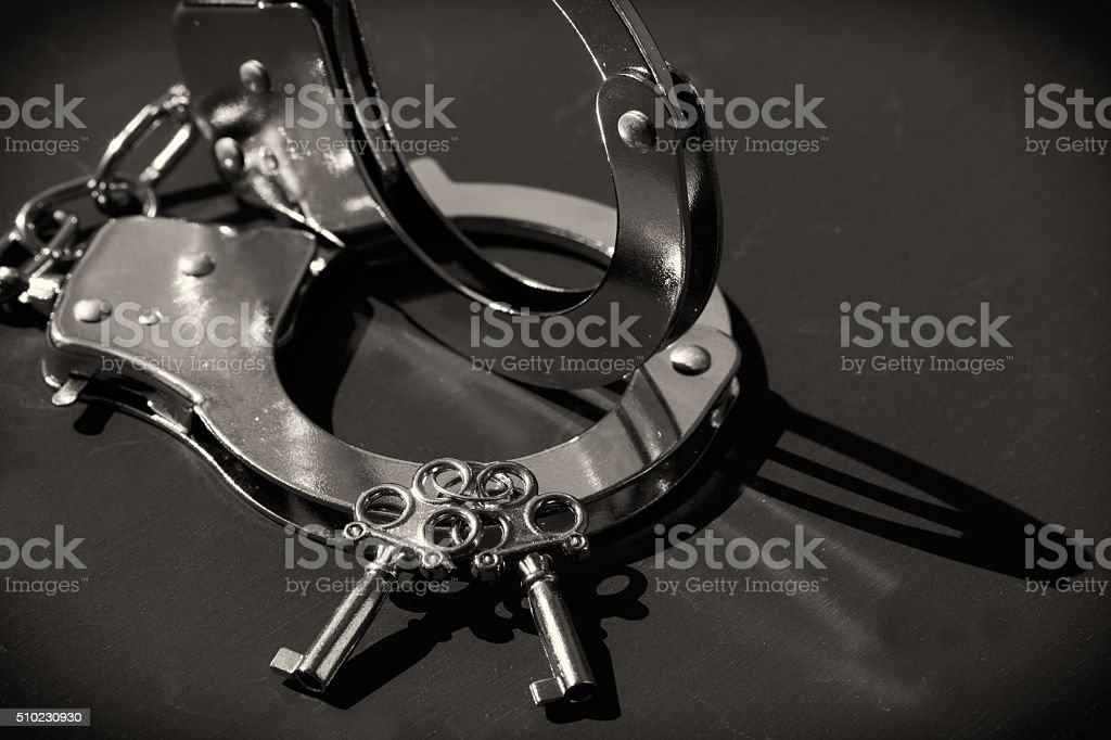 Silver handcuffs and keys stock photo