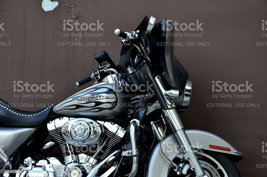 Silver Harley motorcycle against brown wall background stock photo