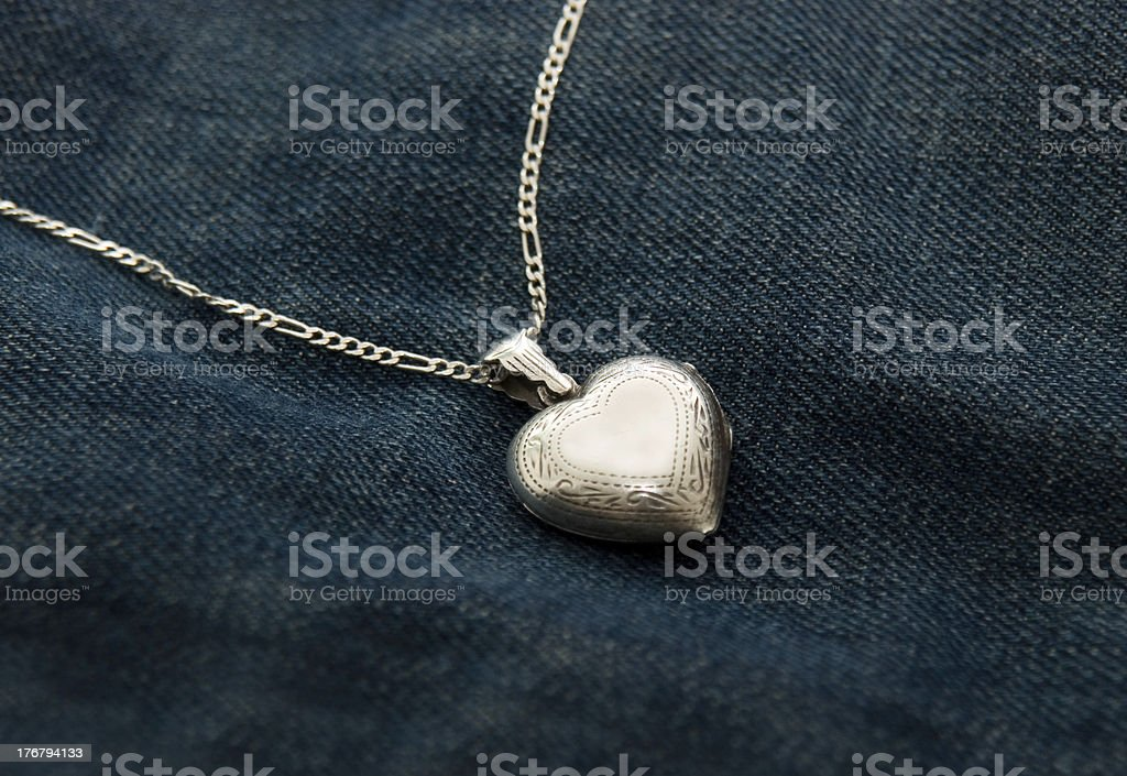Silver Heartshaped Amulet Lying On Blue Jeans royalty-free stock photo
