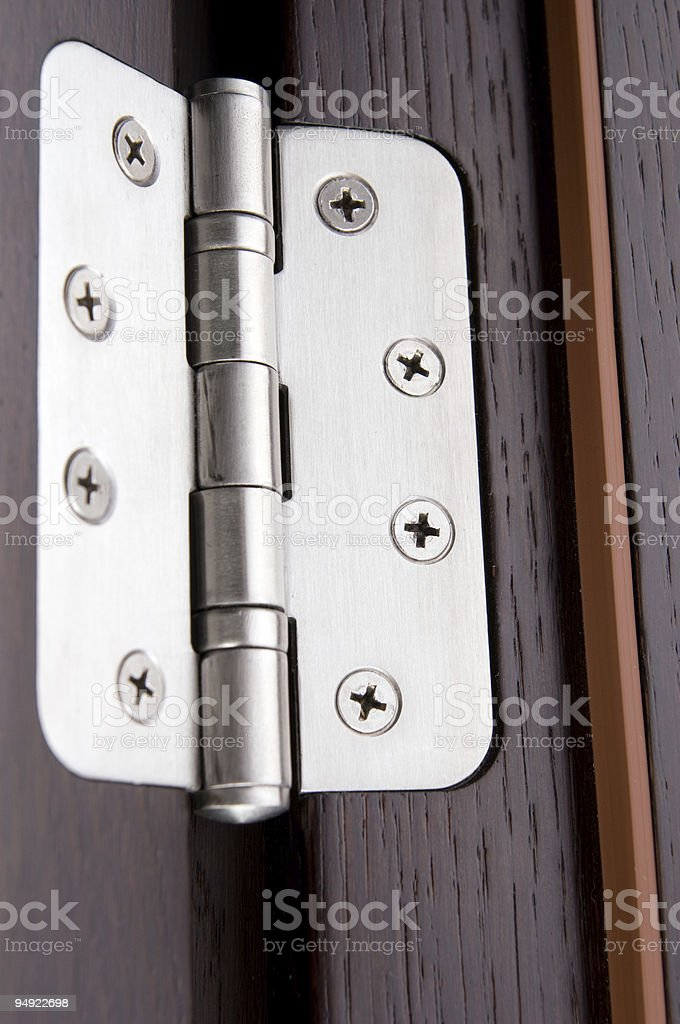 Silver hinge attached to brown door stock photo