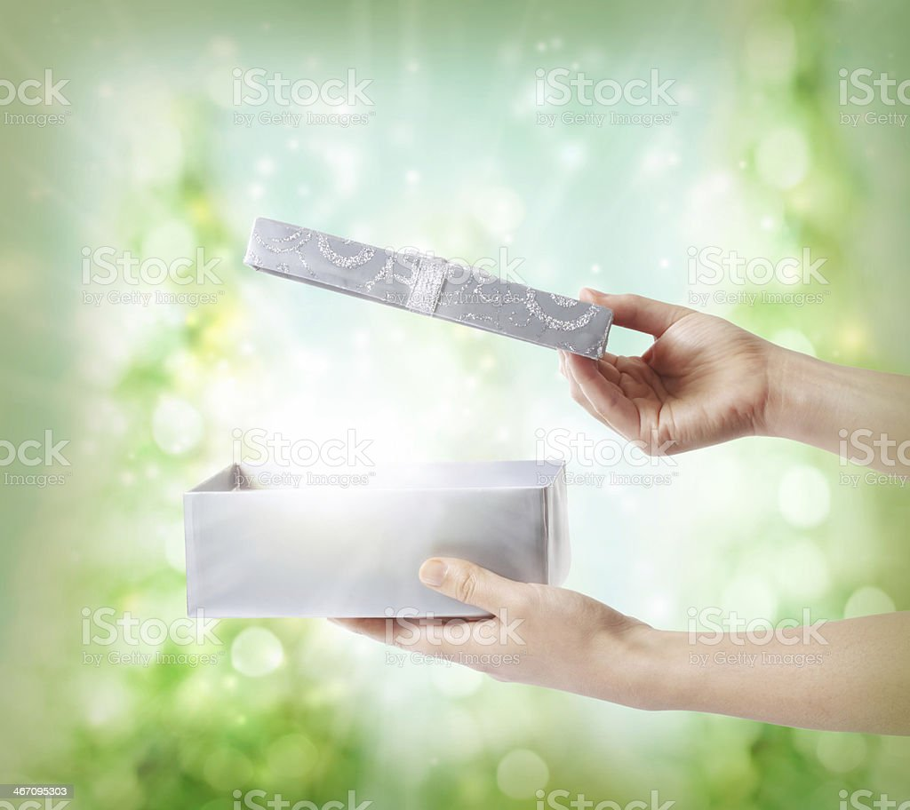 A silver holiday gift box being opened up  stock photo