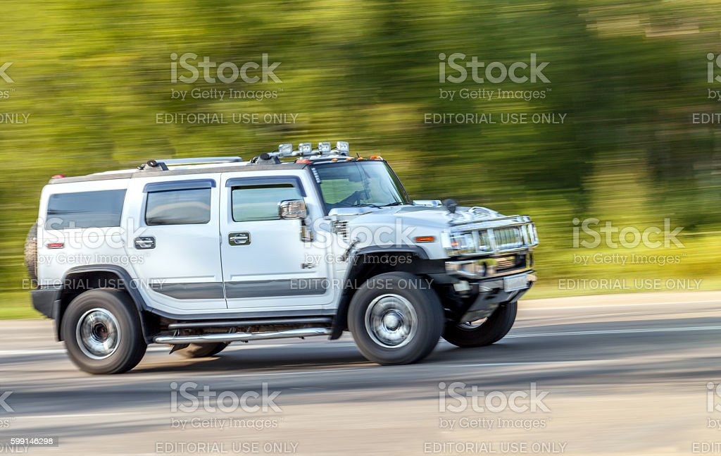 Silver Hummer car rides up the road at high speed. stock photo