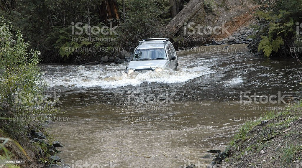 Silver Jeep Cherokee mid stream in creek crossing royalty-free stock photo
