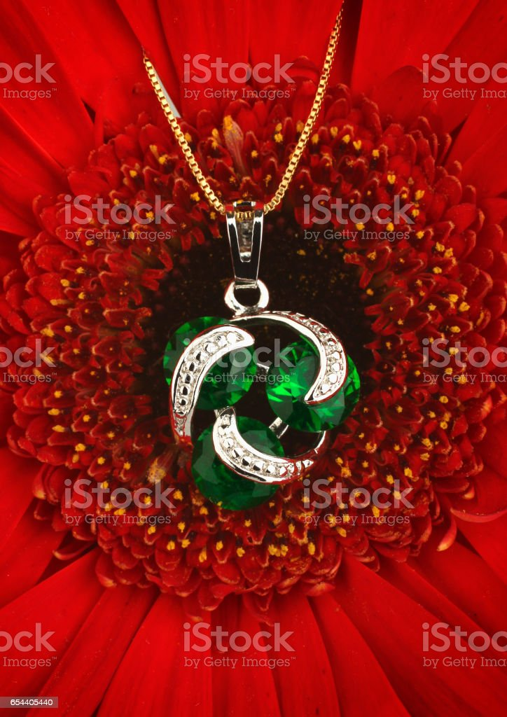 Silver jewellery pendant with diamonds and emerald on flower background stock photo