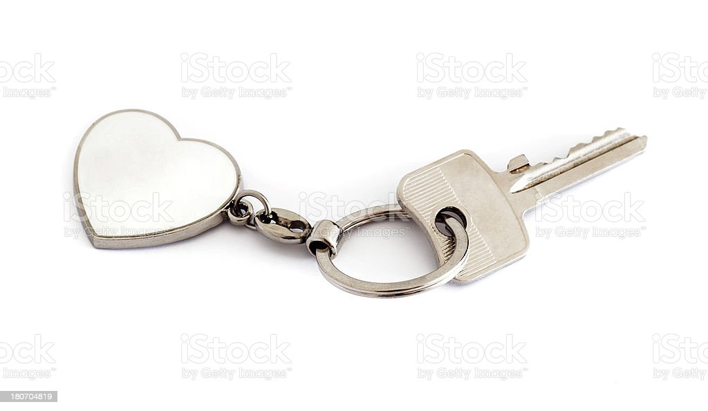 A silver key is attached to a white heart key chain. stock photo