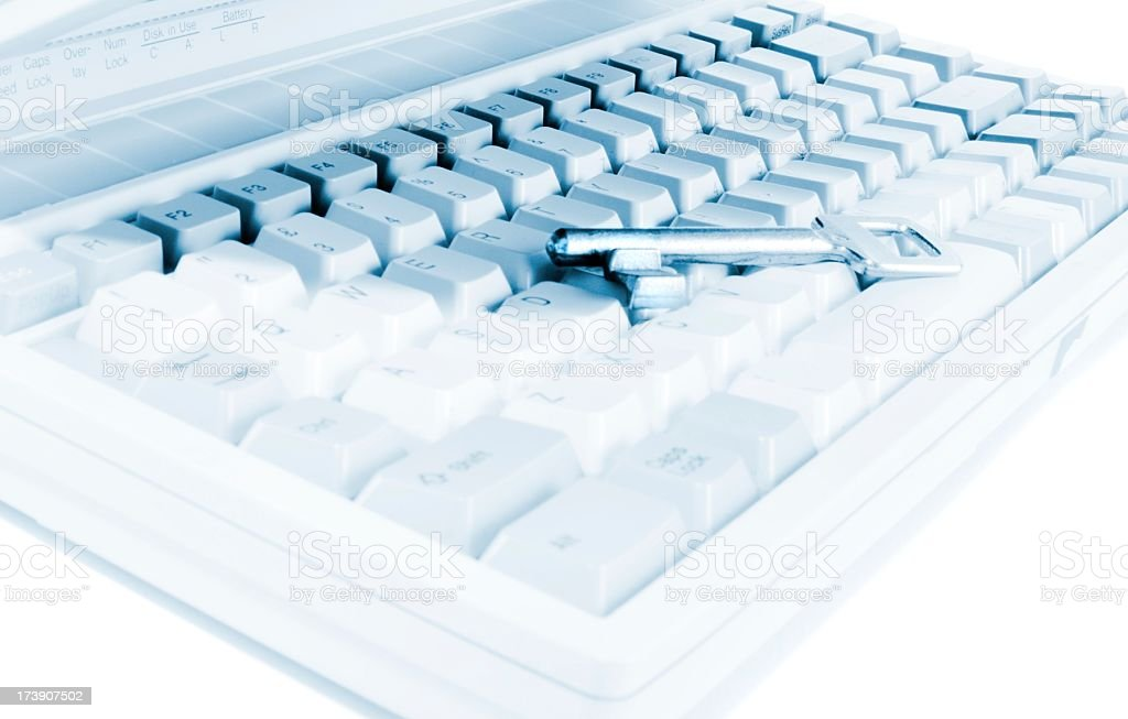 Silver key lying on a whie keyboard, data security royalty-free stock photo