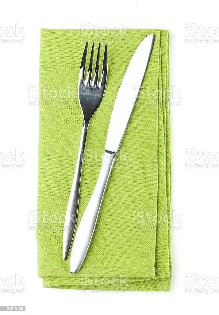 Silver knife and fork on folded green napkin stock photo