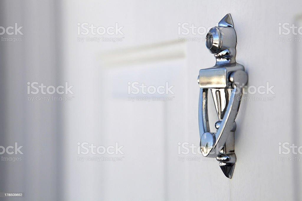 Silver Knocker On White Door stock photo