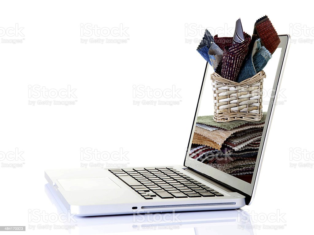 Silver laptop and textiles stock photo