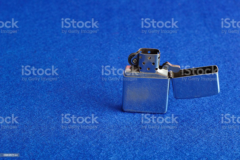 Silver lighter isolated on a blue background stock photo