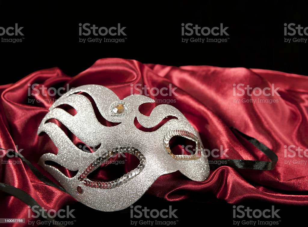 Silver masquerade mask on a red fabric stock photo