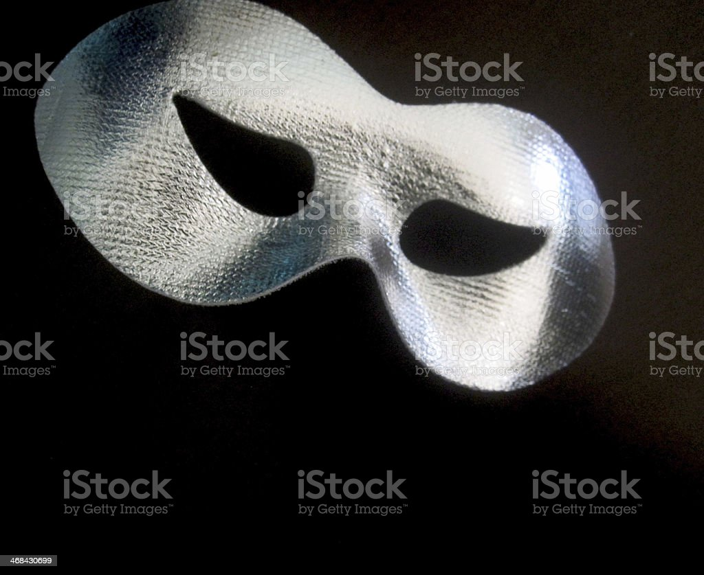 Silver masquerade mask on black stock photo
