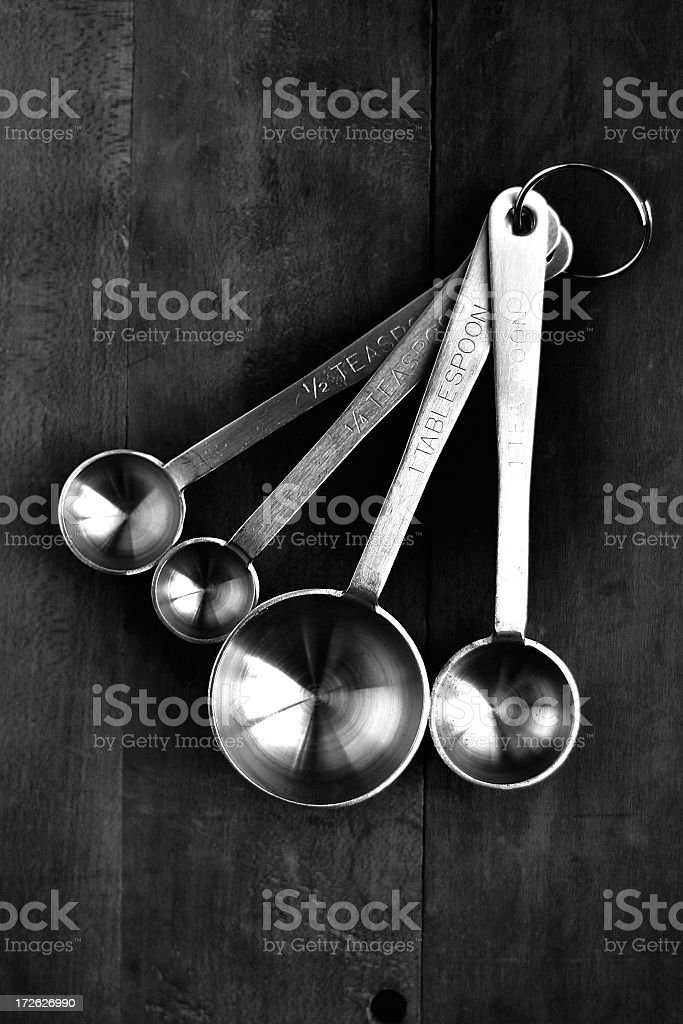 Silver measuring spoons on a wooden background stock photo