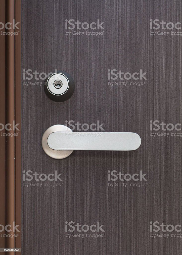 Silver metal door handle and brown wood door stock photo