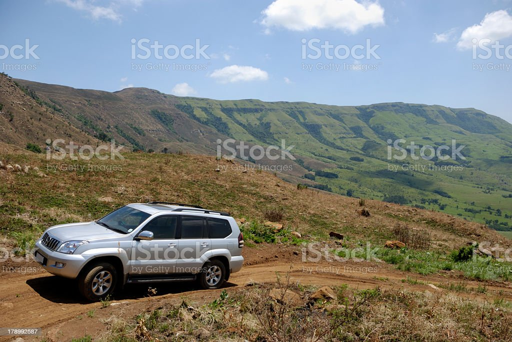 Silver midsize car driving on dirt road stock photo
