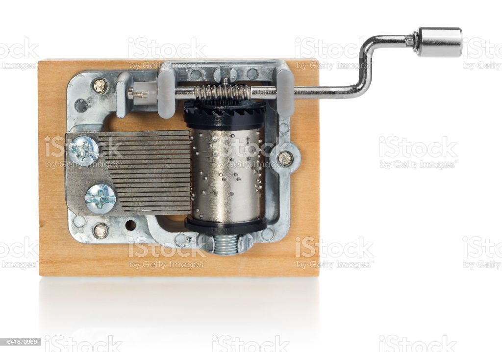 Silver music box mechanism with the handle on a wooden plank. Musical toy in the view from the top on a white background with slight reflection. stock photo