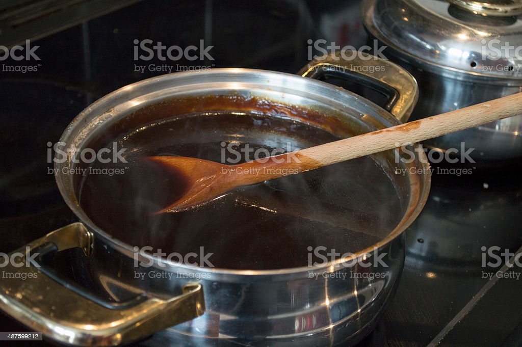 Silver pan of gravy boiling on the stove stock photo