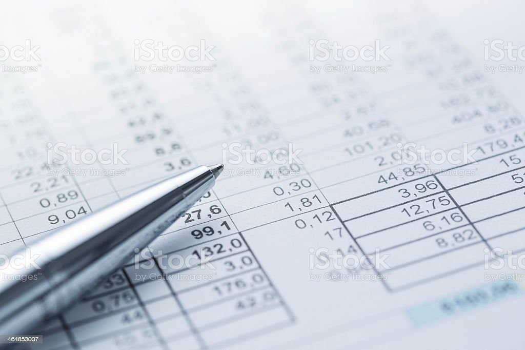 A silver pen on top of an accounting report stock photo