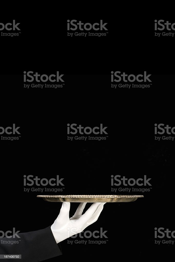 Silver Platter held by white gloved hand/isolated on black-vertical royalty-free stock photo