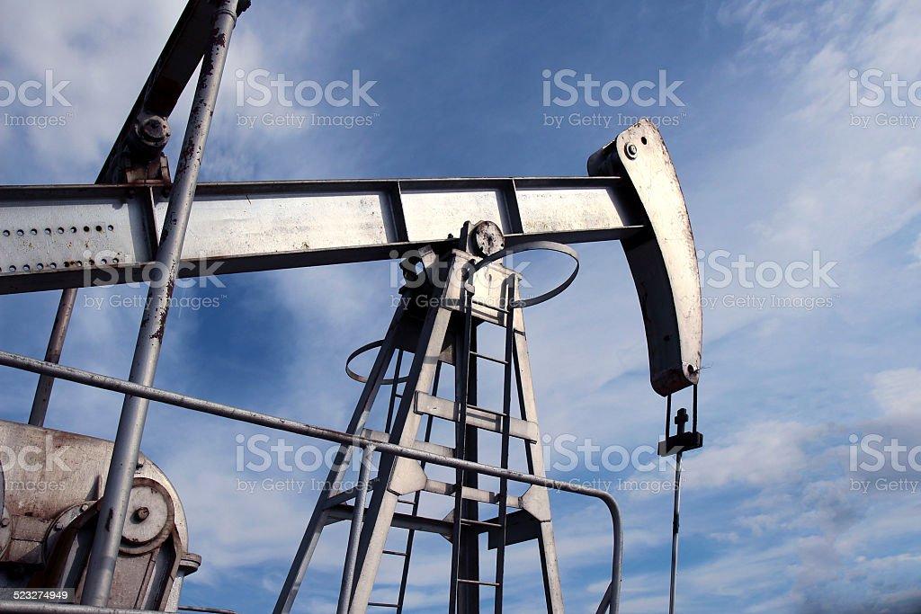 silver pumpjack in crude oil field mine stock photo