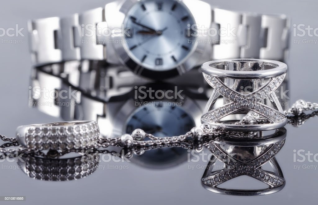 Silver rings and silver chain on background of women's watch stock photo