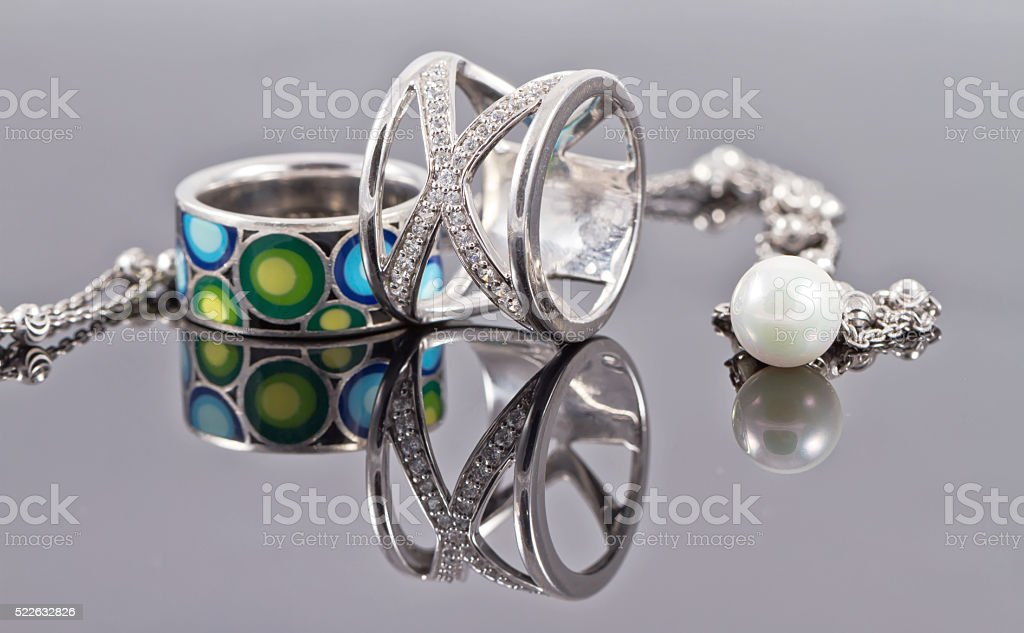 Silver rings of various shapes and silver chain stock photo